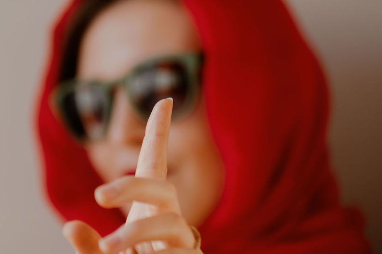 Close-up portrait of woman hand on red finger