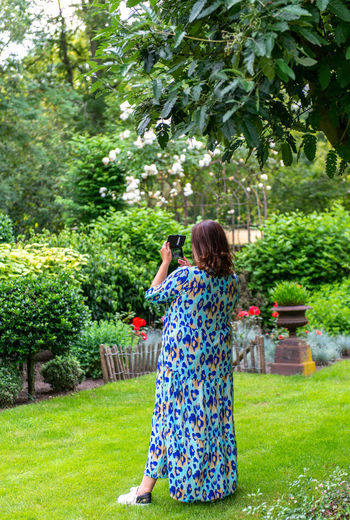 Rear view of woman standing by plants in yard