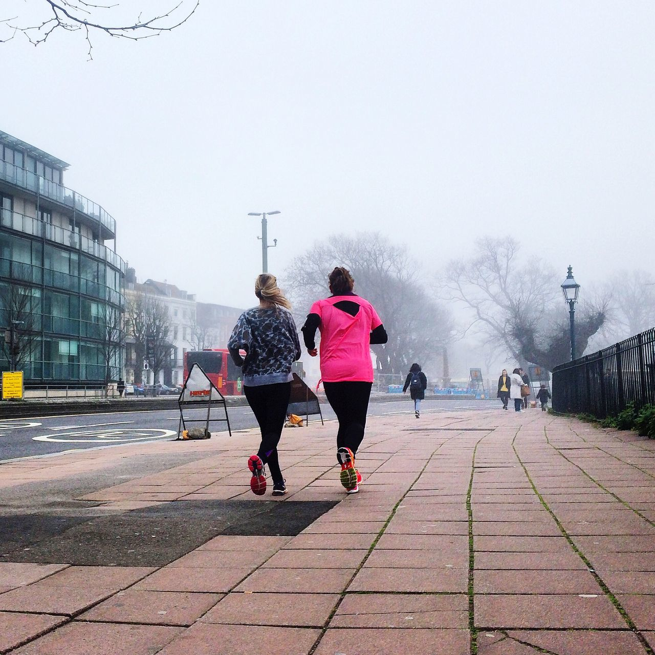 Two women jogging on sidewalk