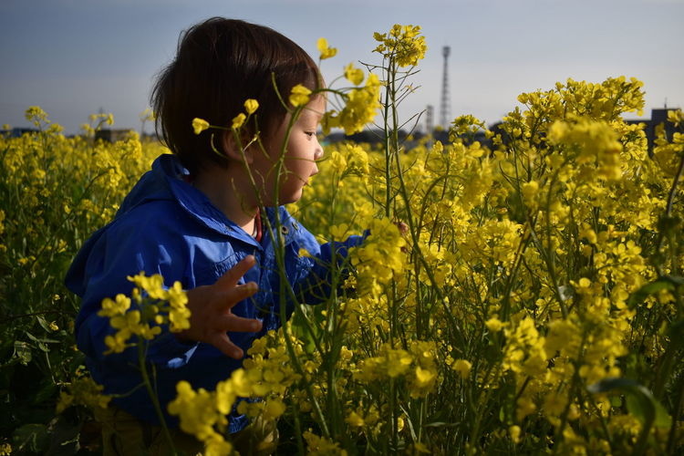 Baby standing on field by yellow flowers