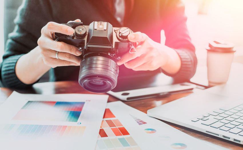 Midsection of design professional holding digital camera at desk in office
