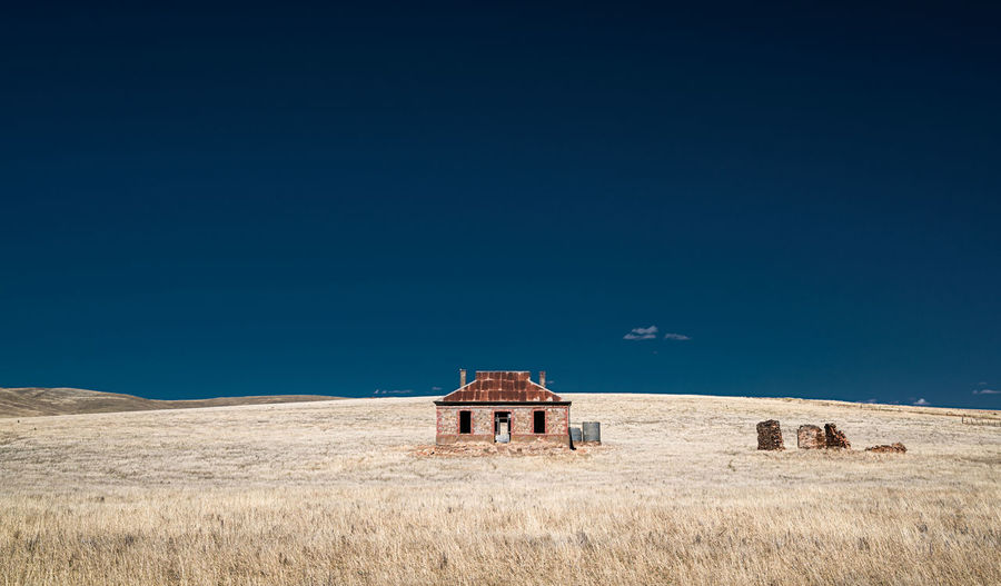 Abandoned house on field against clear blue sky