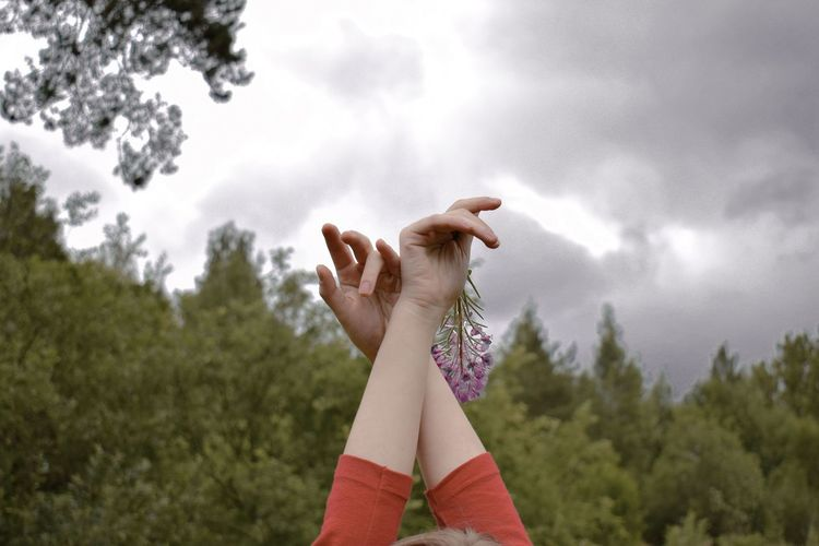 Cropped Hands Of Woman Against Sky
