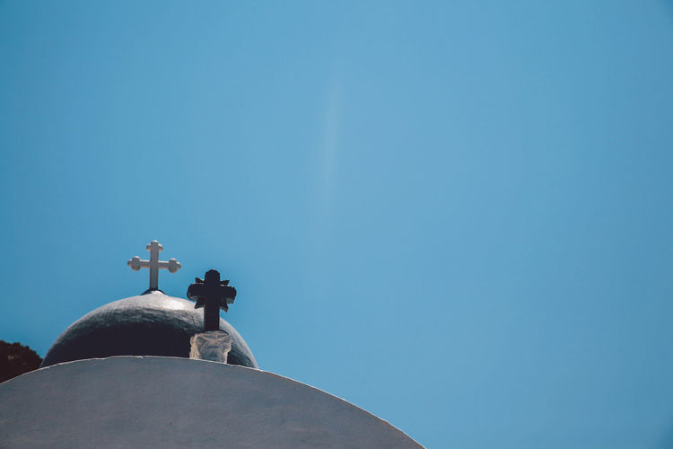 Low angle view of cross on church against clear blue sky at santorini