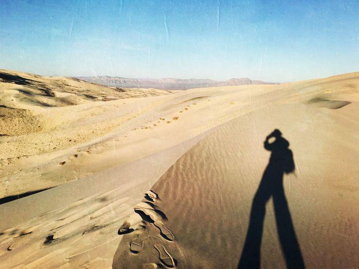 Shadow of man on sand dune against sky