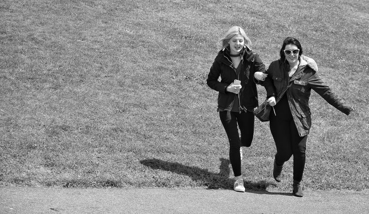 Black And White Monochrome Togetherness Leisure Activity Women Adult Day Happiness Outdoors Full Length Friendship Only Women Young Women Lifestyles Weekend Pursuit Grassy Bank Leaping For Joy Running Joyful The Street Photographer - 2017 EyeEm Awards Street Photography Shadow And Light Live For The Story Two Sommergefühle