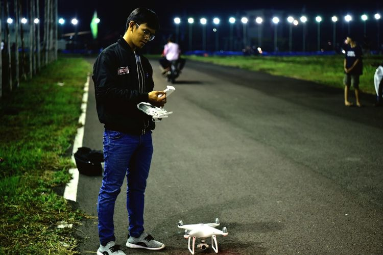 Full length of man with drone standing on road at night