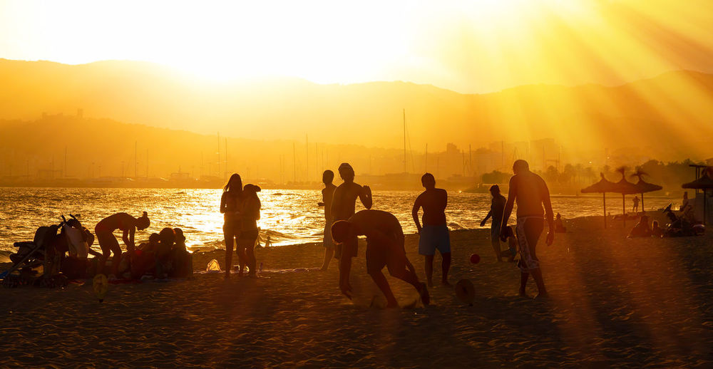 Evening on the beach of Palma De Mallorca, Spain Family Fun Mallorca Palma Palma De Mallorca SPAIN Vacations Activity Beach Destination Group Of People Island Leisure Activity Lens Flare Lifestyles Nature Orange Color Playing Relax Sea Silhouette Sun Sunlight Sunset Water