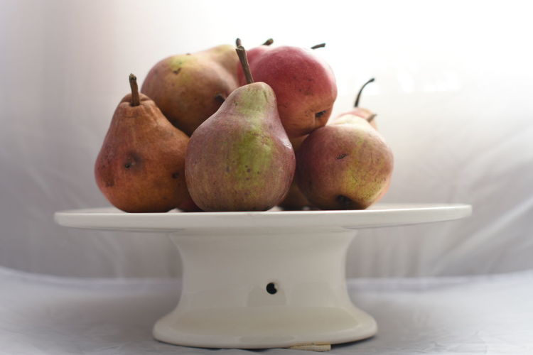 Close-Up Of Pears On Cakestand Against White Background