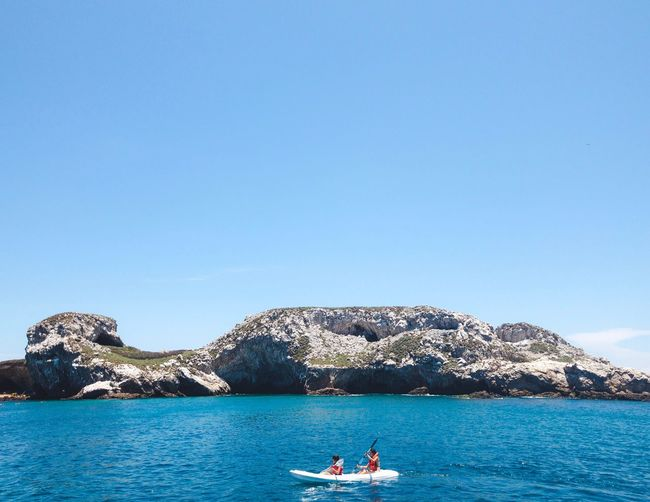 People kayaking in sea against clear blue sky