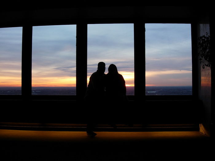 Silhouette Couple Looking Through Window During Sunset