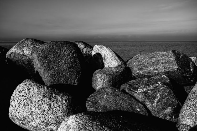 Stack of rocks at sea shore against sky
