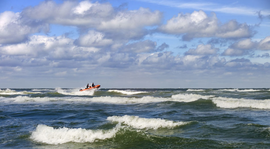 People sailing speedboat in sea against cloudy sky