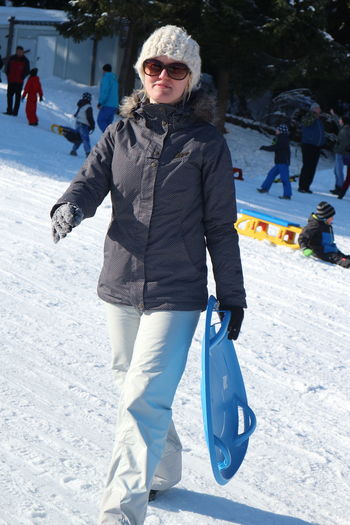 Young Woman Holding Snowboard While Walking On Snowy Field