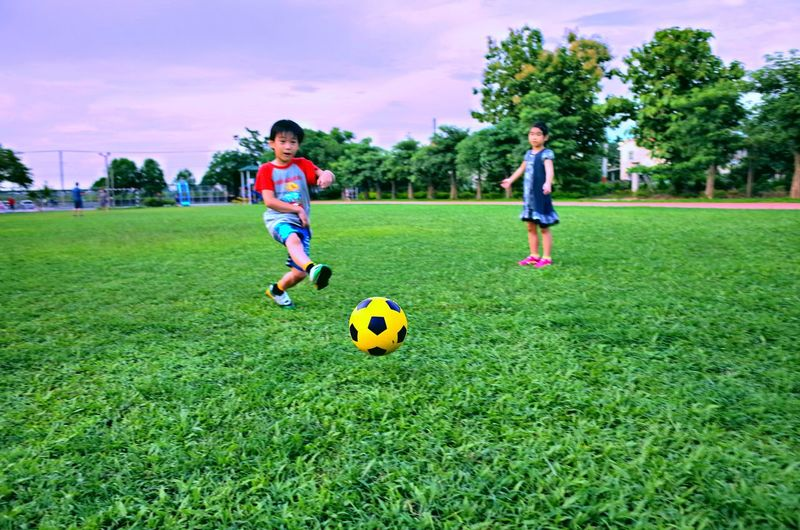 Full length of boy and girl playing soccer with ball on grass against sky