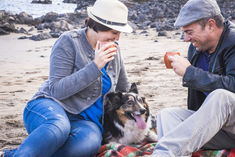 Happy Couple Having Drinks While Sitting With Dog At Beach