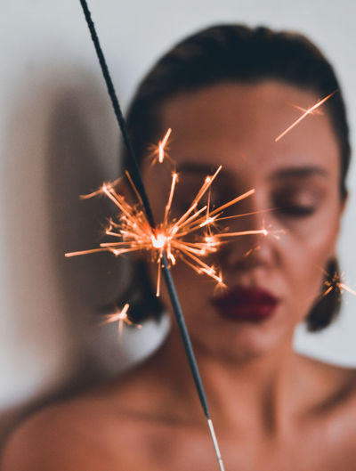 Close-up of woman with lit sparkler at home