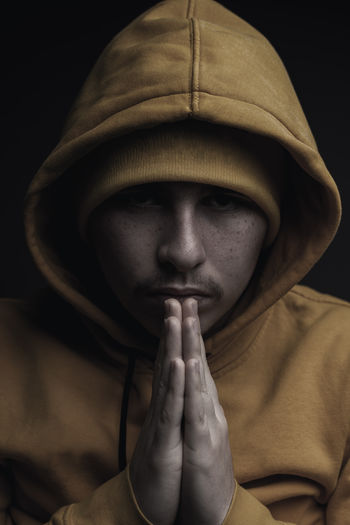 low key portrait of young rapper with yellow hoodie and praying hands Portrait Headshot Studio Shot Indoors  Clothing Praying Close-up Spirituality Front View Religion Belief Believe Praying Hands Rapper Hip-Hop Yellow Low Key Dark Human Face Hands Clasped Hood - Clothing