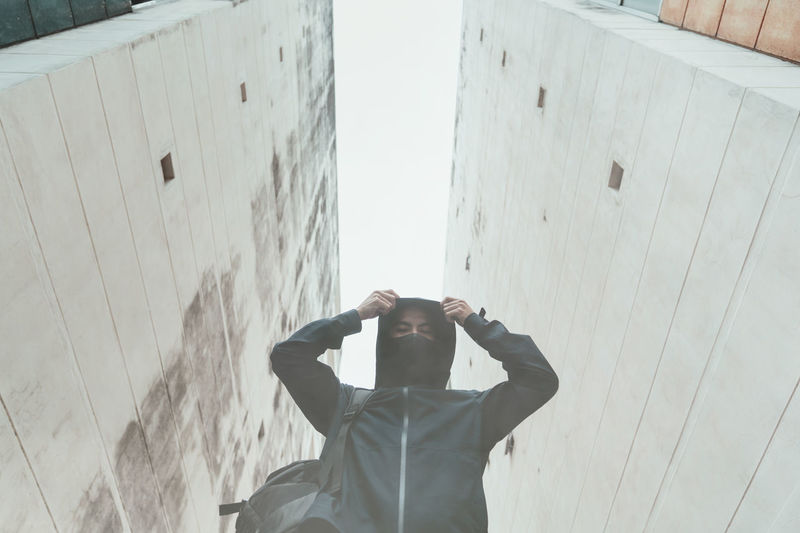 Low angle portrait of man wearing hood standing against buildings