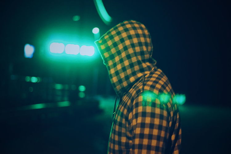 Side view of man wearing hooded shirt against green illuminated light
