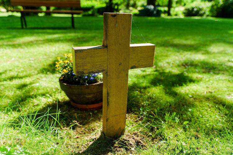 Cross on grass in field