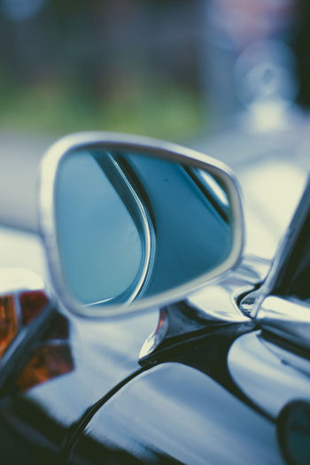 Close-up of sunglasses on side-view mirror
