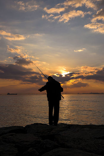 Rear view of man fishing in sea against sunset sky