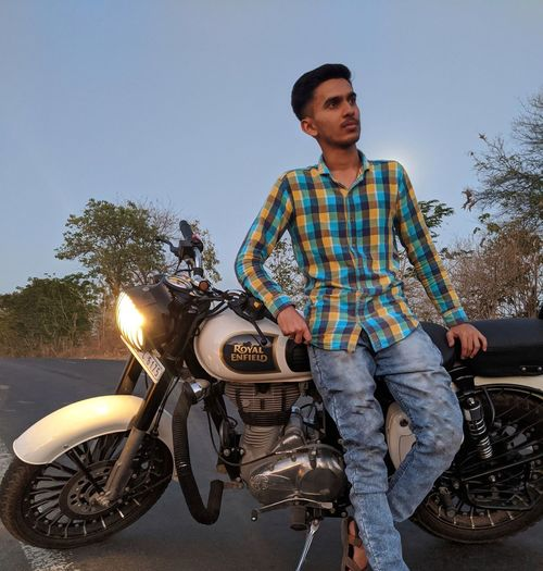 Young man riding motorcycle against sky