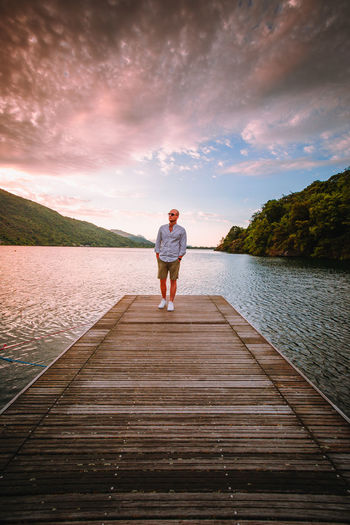 Rear view of man standing on pier over lake against sky