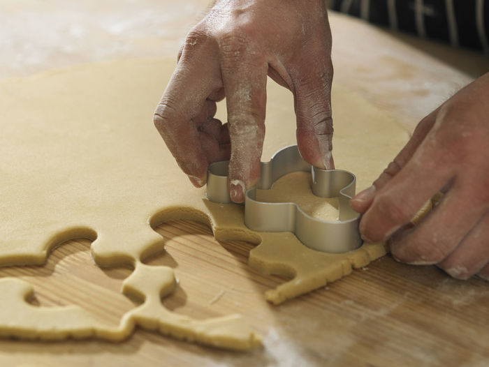 Cropped Hands Of Chef Cutting Dough With Pastry Cutter At Table
