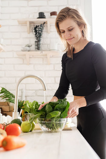 Young woman cleaning vegetables in kitchen