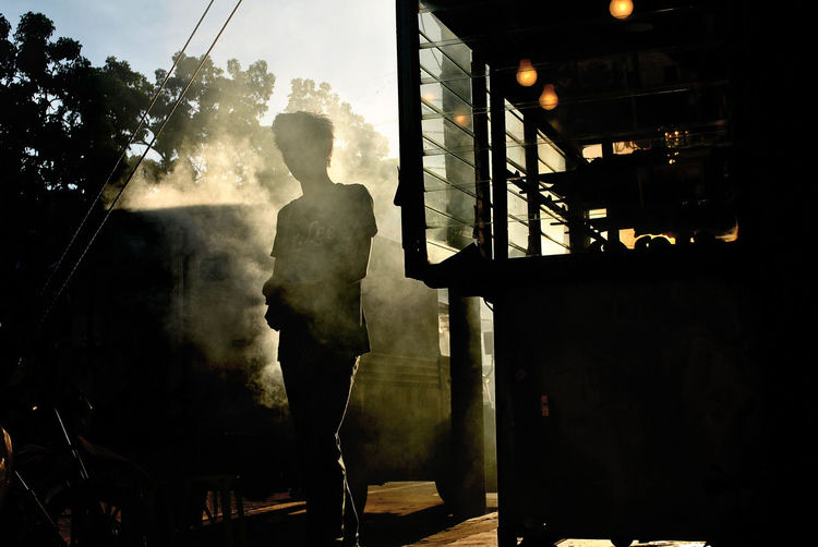 Street food vendor standing amidst smoke in city