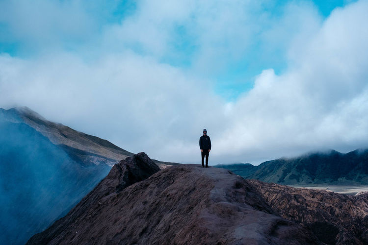 Young man standing on mountain against cloudy sky