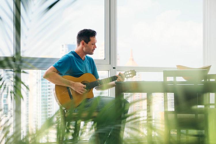 Man playing guitar in glass window