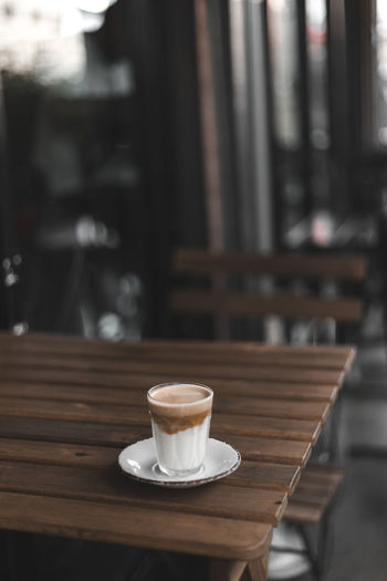 Coffee cup served on wooden table in cafe
