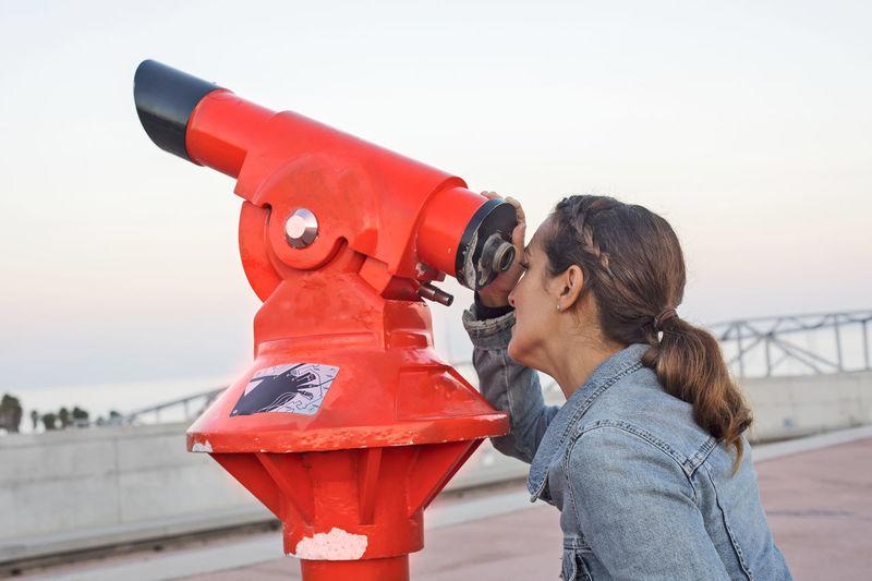 Side view of woman looking through binoculars against clear sky