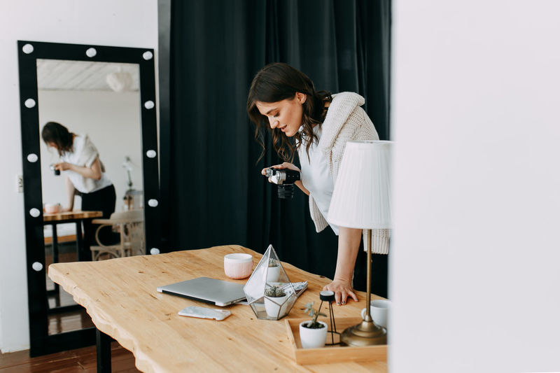 Woman looking at camera while standing on table