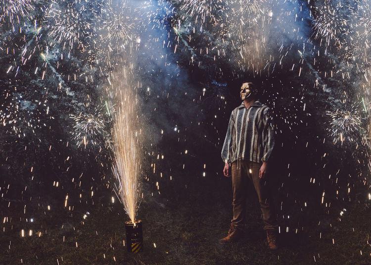 Man standing amidst firework display at night