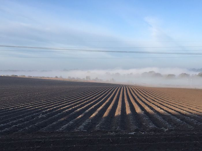 Scenic View Of Plowed Field Against Sky