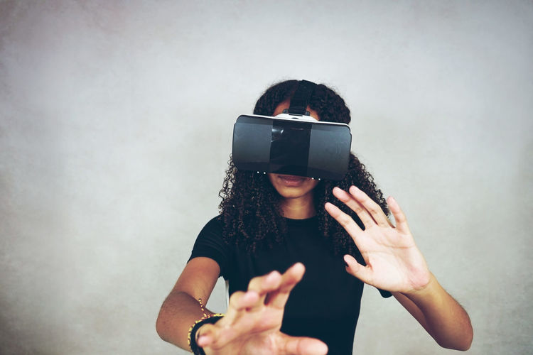 Woman wearing virtual reality simulator while gesturing against wall