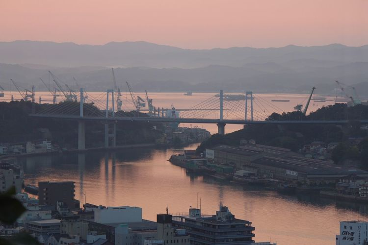 High Angle View Of River Amidst Cityscape Against Sky During Sunset