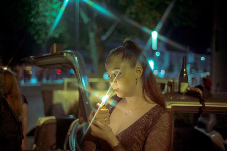 Portrait of woman looking at illuminated camera at night