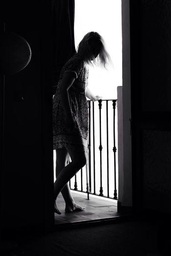 Full Length Of Woman Standing On Balcony Seen Through Doorway