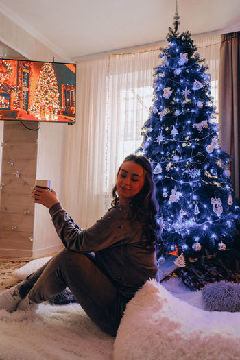 Beautiful young girl sitting next to the christmas tree. new year decoration. home interior. winter