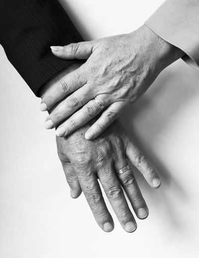 Cropped Image Of Senior Couple Hands On Table