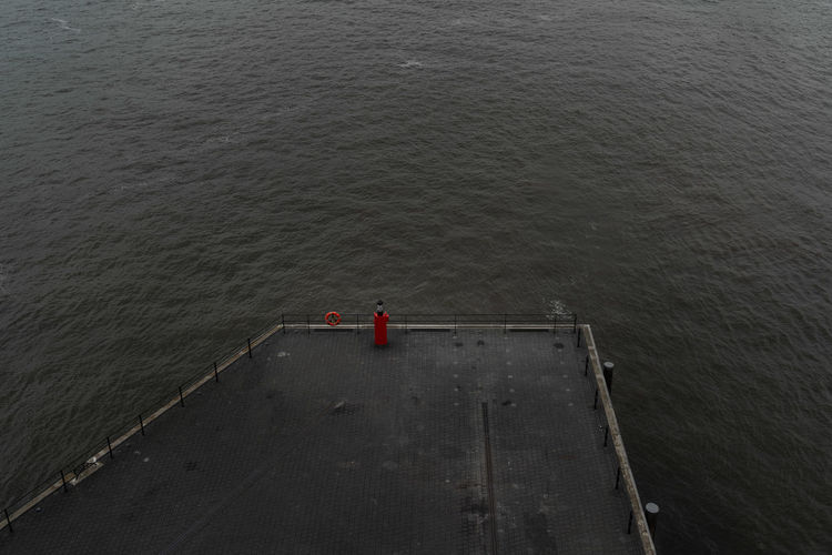 High angle view of man standing on railing against sea