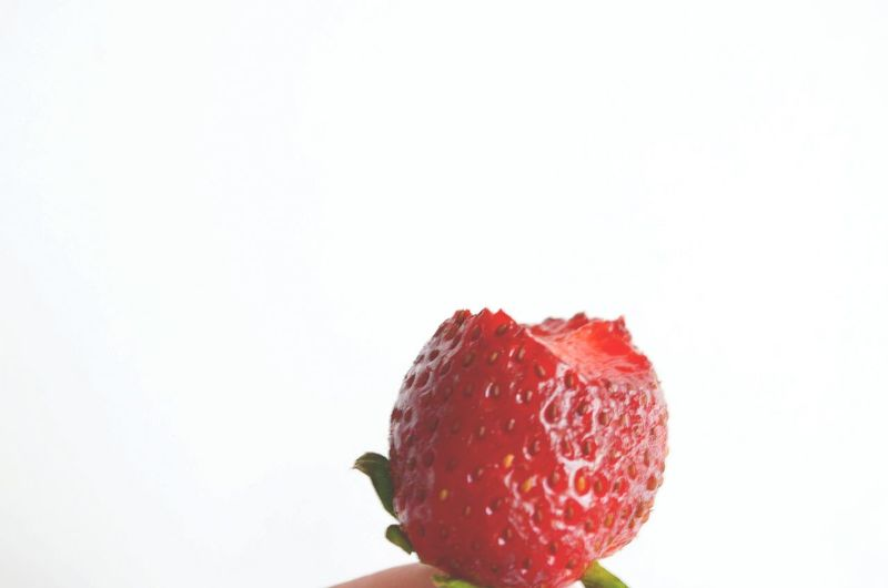 Eaten strawberry against white background