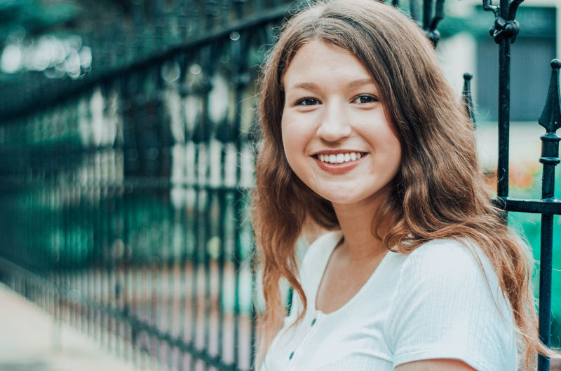 Portrait of smiling teenager standing by railing outdoors