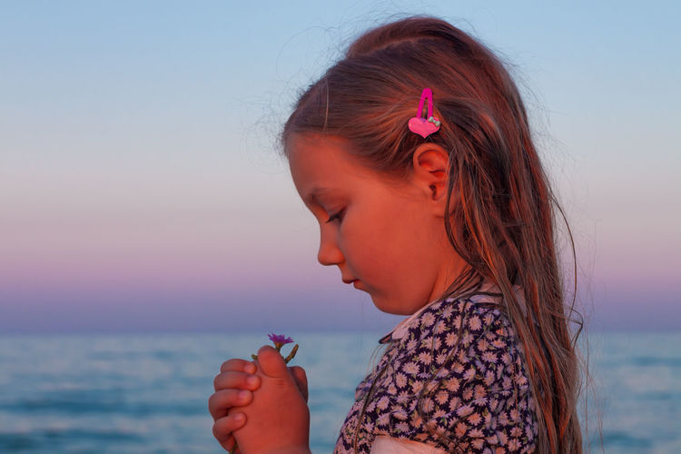 Adorable little girl looks on flower on beach.cute child with wet long hair in dress smelling flower