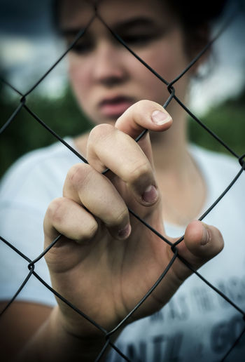 Close-Up Of Girl Seen Through Chainlink Fence